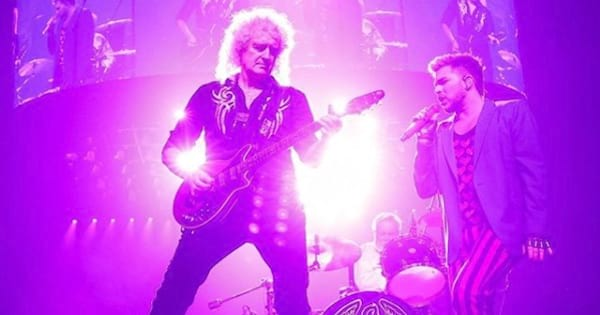 queen with adam lambert performing on stage