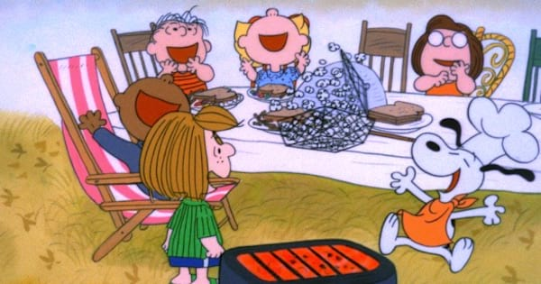 charlie brown and friends gathered seated around thanksgiving table