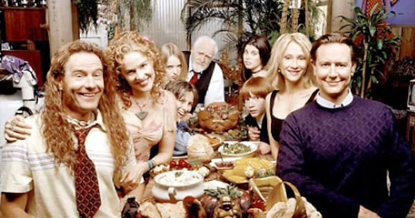 family sitting at thanksgiving table smiling