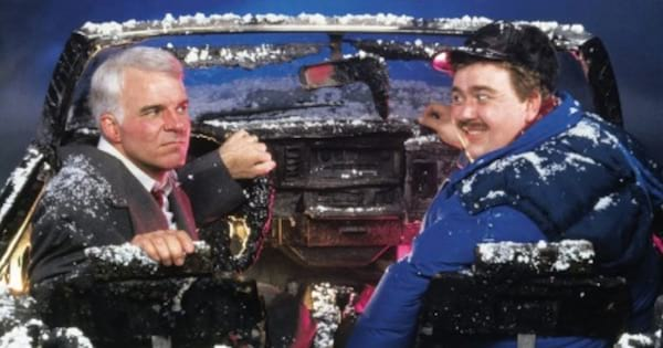men in the car together in the snow facing backwards