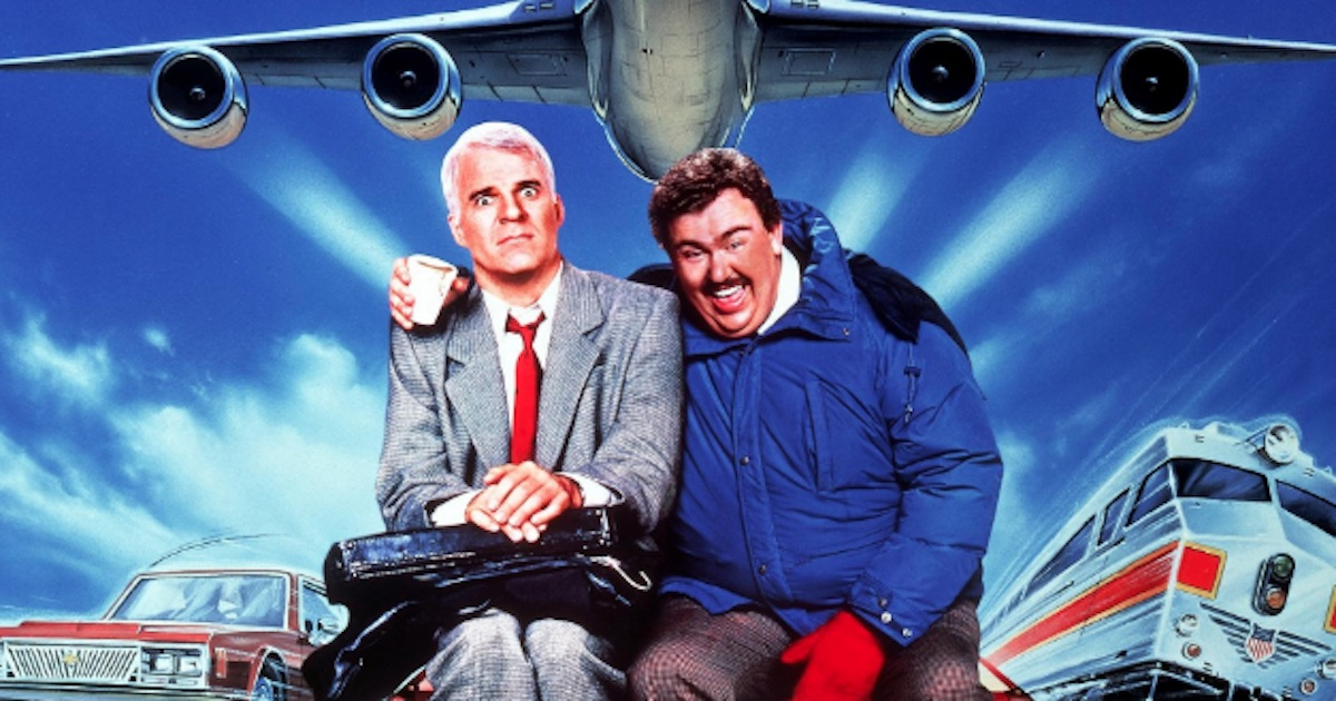 men sitting under plane one smiling with his arm around the other who is unhappy
