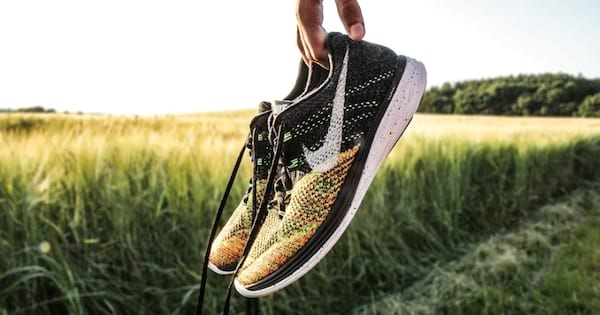 man's hand holding nike shoes in grass field