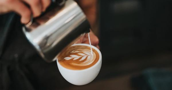 person pouring coffee from metal cup into mug