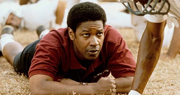 denzel washingon on the grass on football field in remember the titans