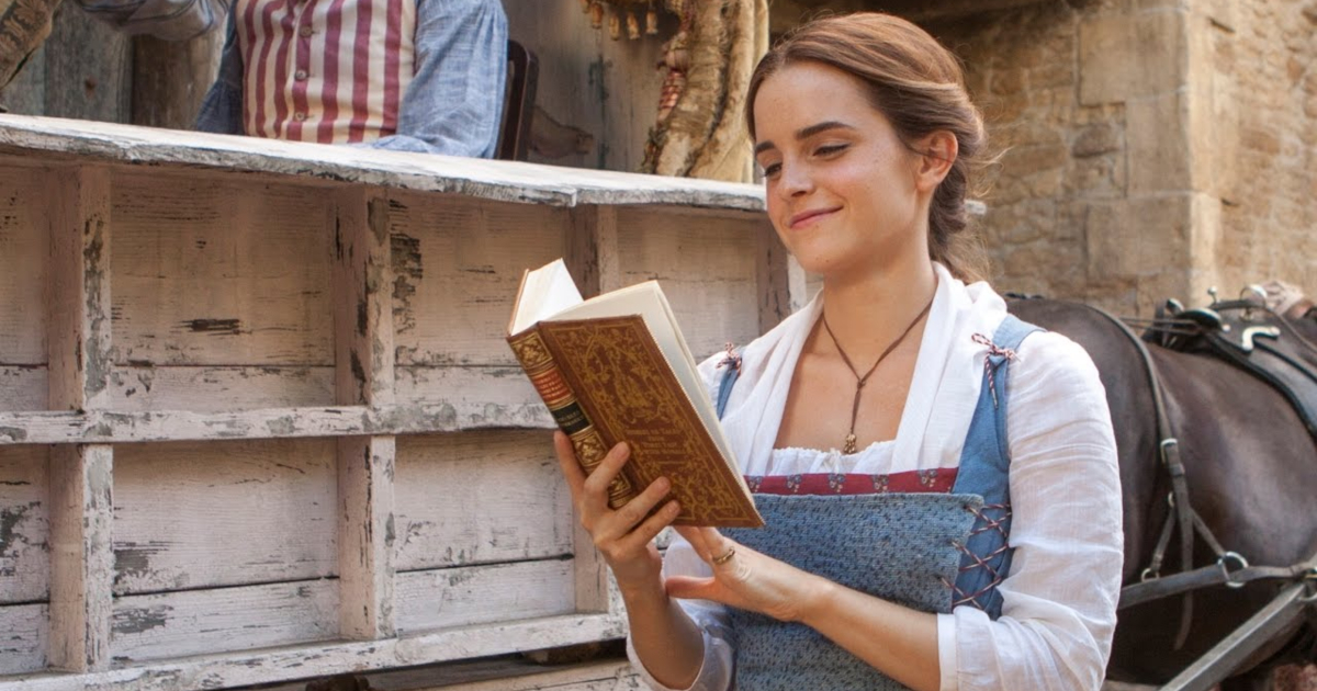 Emma Watson as Belle reading a book in Beauty and the Beast