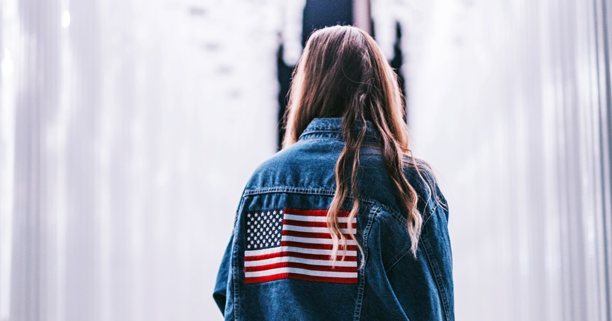 Democrat Instagram Captions, photo of a white woman with blonde hair facing away from the camera and wearing a jean jacket with an American flag, politics