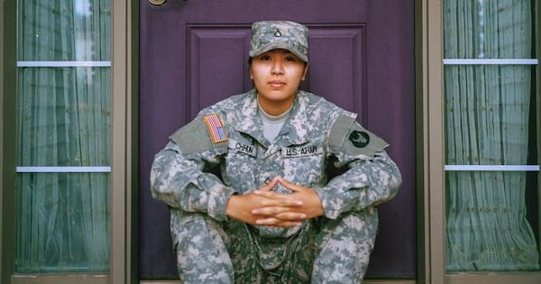 Army Instagram Captions, an Asian man in army drabs sitting on the front stoop of a house, career
