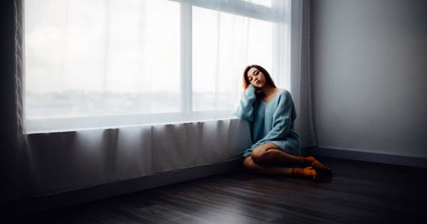 Best SAD Lamps, an Asian woman with seasonal depression sits on the floor by the window, health