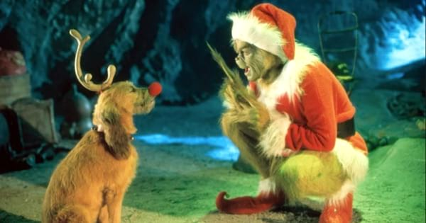 the grinch bent down talking to his dog dressed like a reindeer, christmas movie