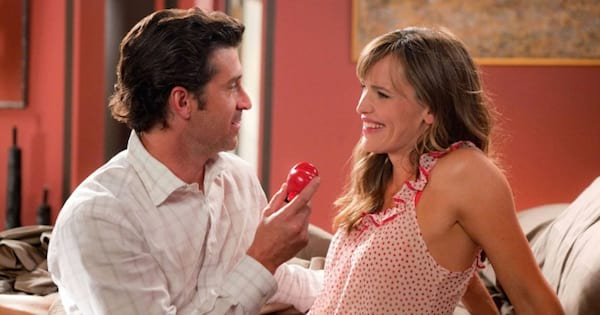 man leaning into woman handing her a red heart, movies romance comedy