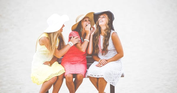 Three girls laughing while sitting on a bench.