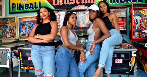 The four women from The Fourtress standing in front of pinball machines