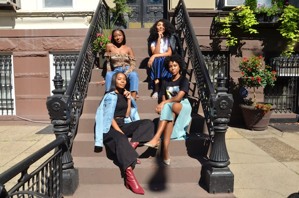 The women of The Fourtress sitting on a front porch in New York
