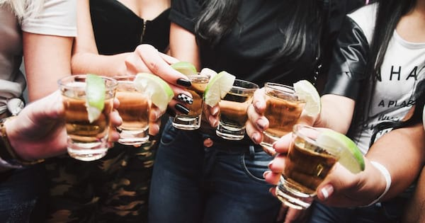 Tequila Instagram Captions, closeup of a group of women holding shots of tequila with lime wedges, food & drinks