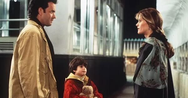 sam baldwin and annie reed standing outside across from each other with sam's son holding a teddy bear, romantic comedy movies
