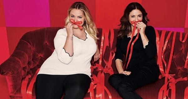 two models for dressbarn sitting on red couch holding up bows to their mouths, fashion