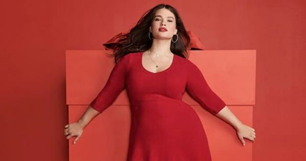 torrid model wearing a red dress smiling against a red background, fashion