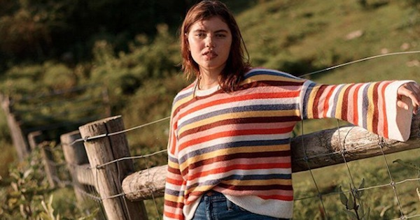 madewell model in colorful sweater posing by a field, fashion