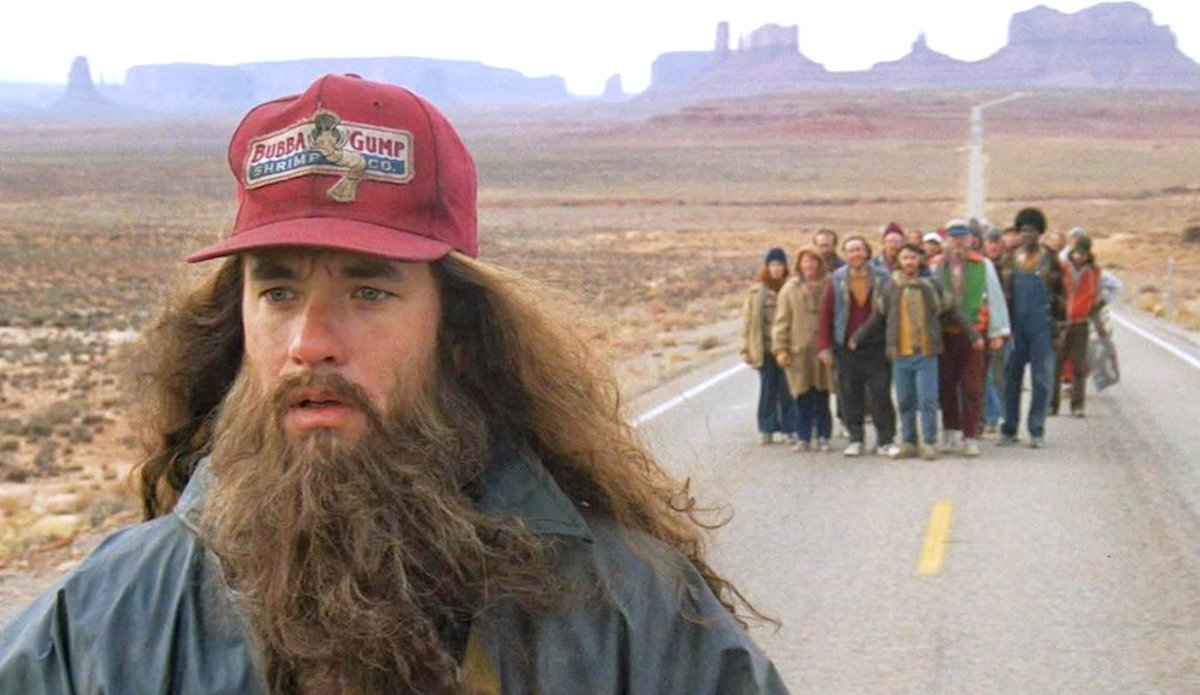Forrest Gump with long hair and a beard, wearing a Bubba Gump shrimp hat, running from a crowd of people. Hero, movies, classic, forrest gump, travel, adventure, nature, tom hanks