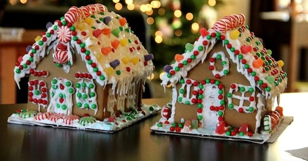 two gingerbread houses decorated with frosting and candy, christmas