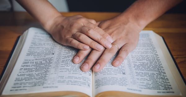 A person with their hands on a bible.