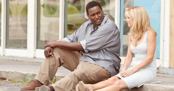michael oher and leigh ann touhy sitting outside on curb talking in the blind side, southern movies