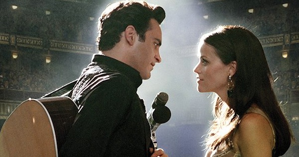 johnny cash on stage with guitar and microphone standing next to a woman, southern movies