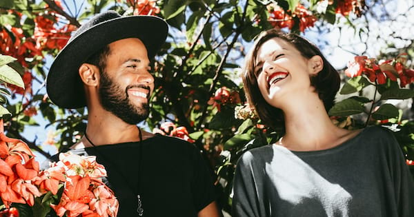 Hallmark Movie Quotes Instagram Quotes, an interracial couple laugh outside together surrounded by orange flowers, movies