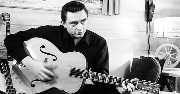 johnny cash playing guitar in a black and white photo, Music