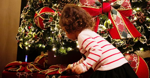 Gift Ideas For Your Niece, a young girl bends down near Christmas gifts under the tree, family