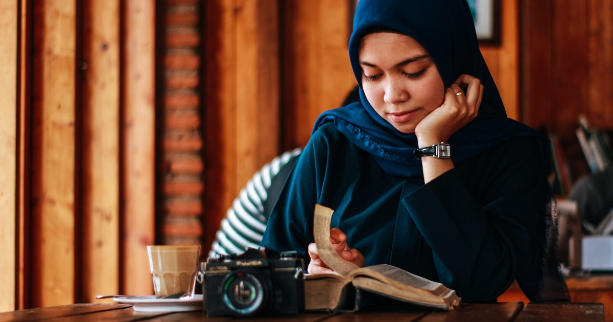 Books to Read When You're Grieving, a woman wearing a hijab sitting at a table reading a book, books