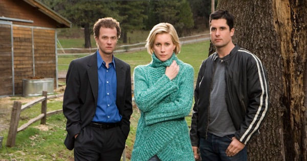 cody, faith, and her husband standing outside in front of a tree in the christmas card movie, hallmark