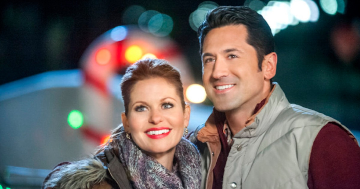 man and woman dressed warm standing outside smiling in Christmas under wraps, hallmark movies