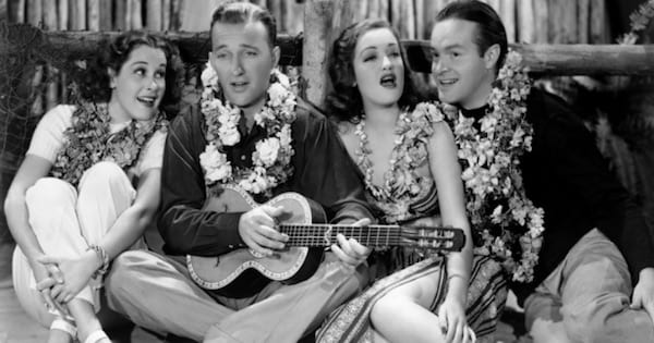 men and women playing ukulele sitting on the ground, bing crosby movies