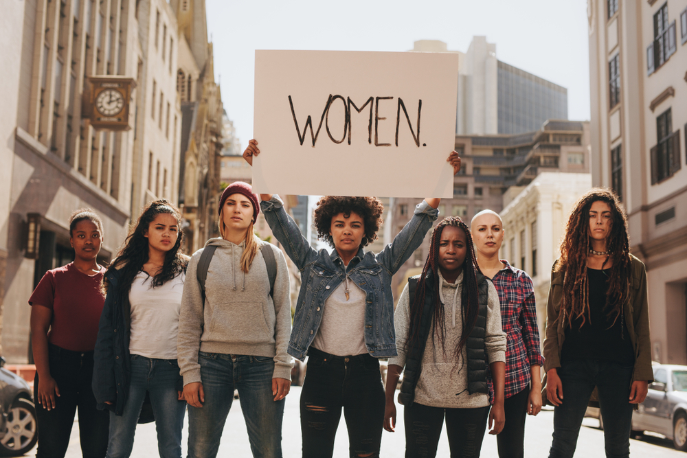 Group of women marching on the road in protest. Young woman holding a protest sign about women empowerment