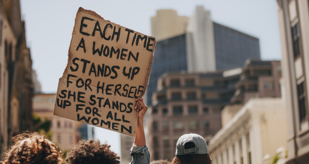 Group of demonstrators on road with a signboard saying each time a woman stands up for herself she stands up for all women. Activist demonstrating women power.