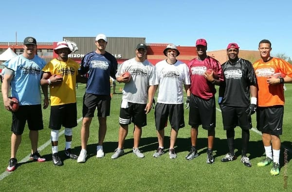 Kurt Warner posing with players at his Ultimate Football Experience