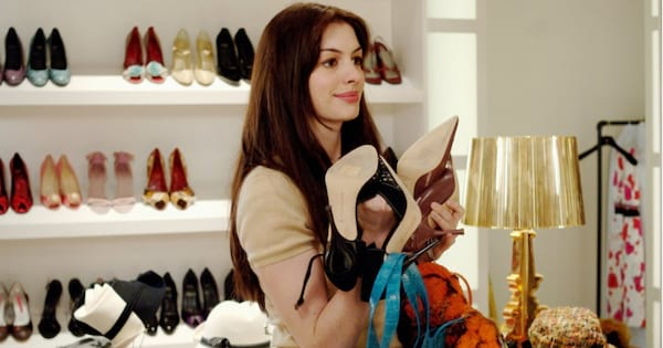 Andy holding a ton of shoes and accessories in her hands during a scene from The Devil Wears Prada