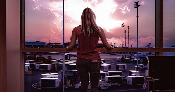Airport Instagram Captions, a white blonde woman wearing jeans and a tank top stares out of the window at an airport, travel