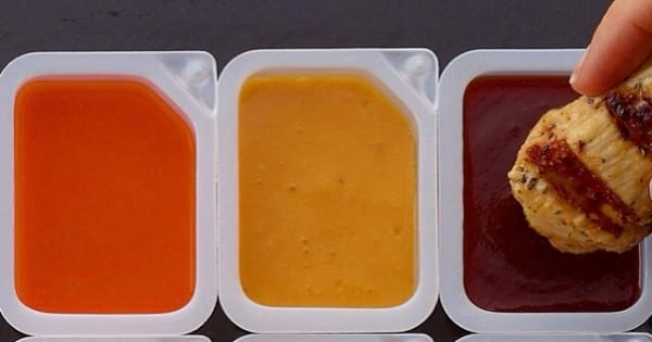 dipping chicken into opened chick fil a sauce packets