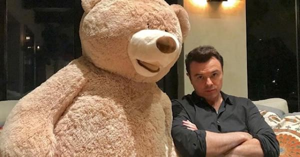 seth macfarlane sitting on couch with life size teddy bear