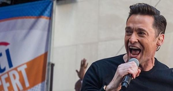 hugh jackman holding microphone with his mouth open