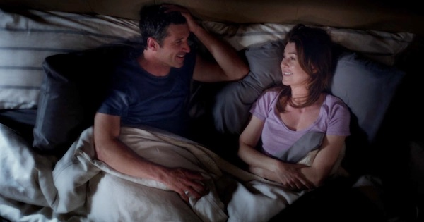 Derek and Meredith laying in bed together smiling
