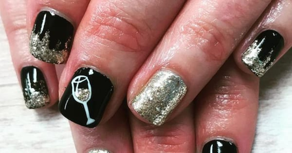 Girl showing off her gold and black New Year's Eve nails