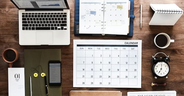 Image of an organized desk with calendar, planner, and laptop.