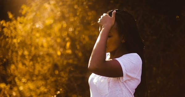 How Stress Is Bad For Your Health, a black woman with long straight hair wearing a white t-shirt holds her forehead, health