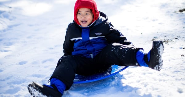Sledding Instagram Captions, a young Asian girl in a blue snowsuit sleds down a hill, fitness, family
