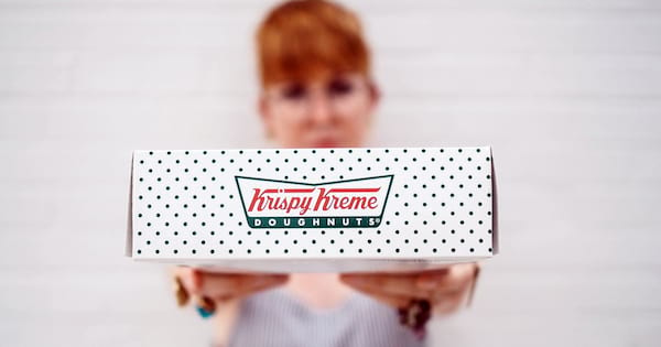 Krispy Kreme Instagram Captions, image of a white woman with red hair holding out a box of Krispy Kreme donuts, food & drinks