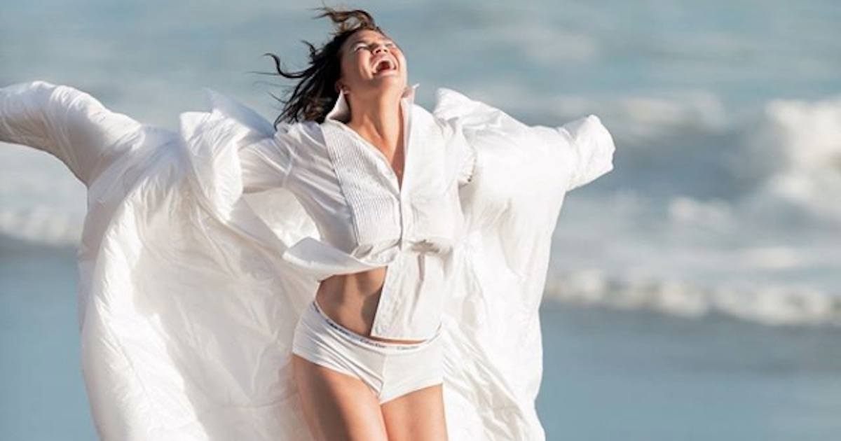 chrissy teigen wearing flowing white outfit running on the beach laughing