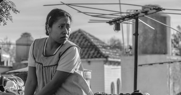 black and white image of a woman standing outside in roma, 2018 movies